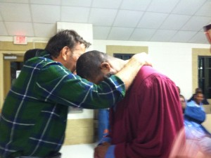 Dale Perkins prays with one of the men to accept Christ